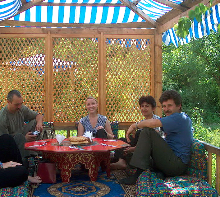 Eating at a tapchan, a raised platform with a low table and cushions, in Crimea, Ukraine